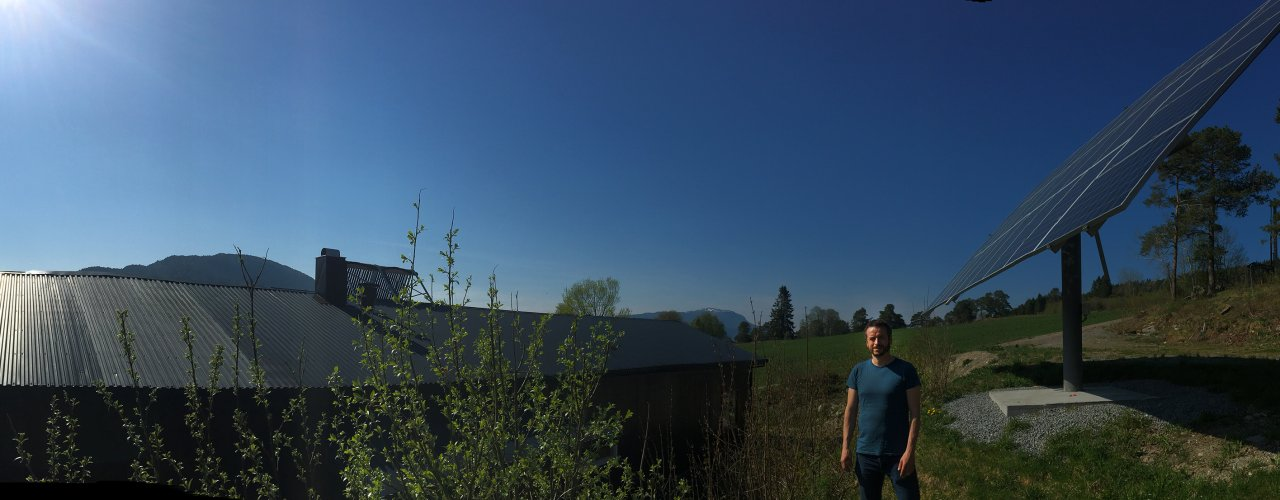 Ingvar Kvande foran det tracker-baserte solcelle-anlegg (9 kWp) på Tingvoll gard (Foto: Anita Land)